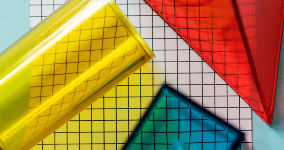 Primary colour geometric shapes over grid paper
